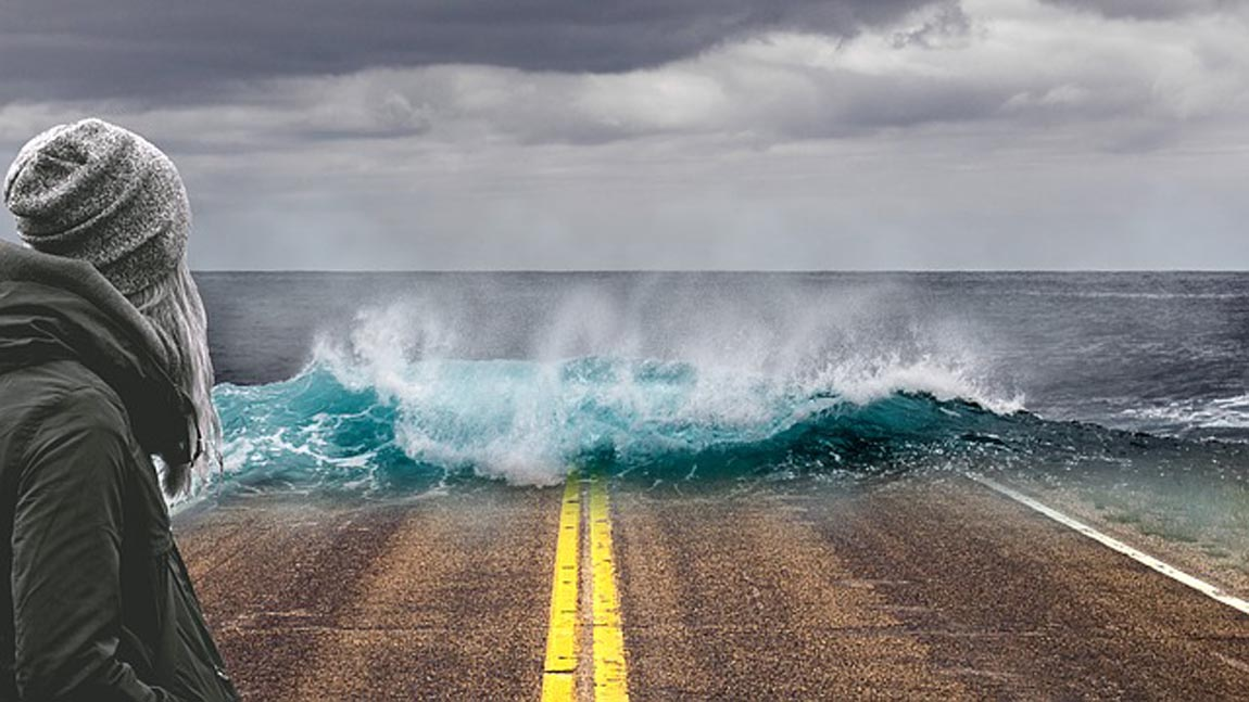 waves crashing over road, implying rising ocean levels